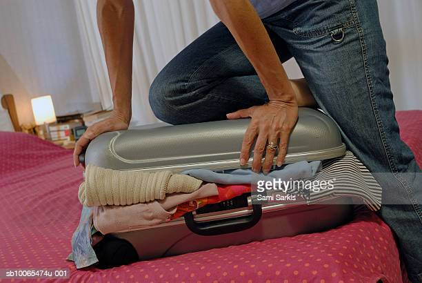 Woman trying to close overflowed suitcase on bed, mid section
