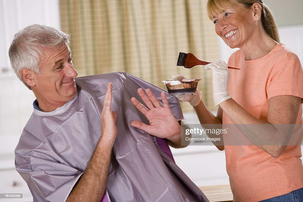 Woman trying to color man's hair : Stockfoto