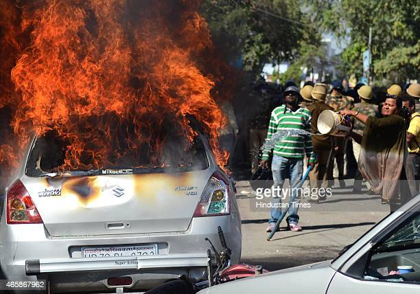 A woman trying to douse the car on fire set alight by angry lawyers outside the district court after a police inspector shot a lawyer in the court...