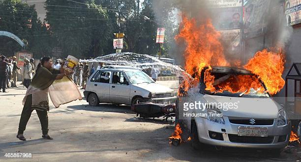 A woman trying to douse the car set aflame by angry lawyers outside the district court after a police inspector shot a lawyer in the court premises...