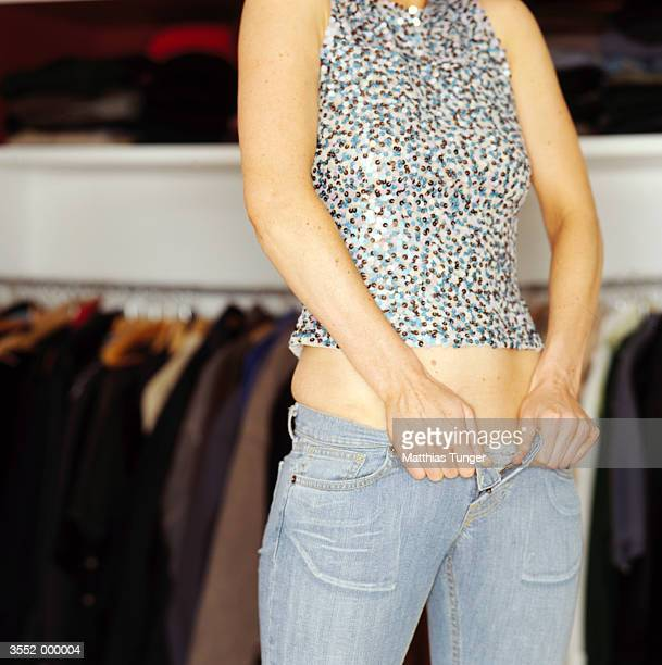 woman trying to fasten pants - hands in her pants stock photos and pictures