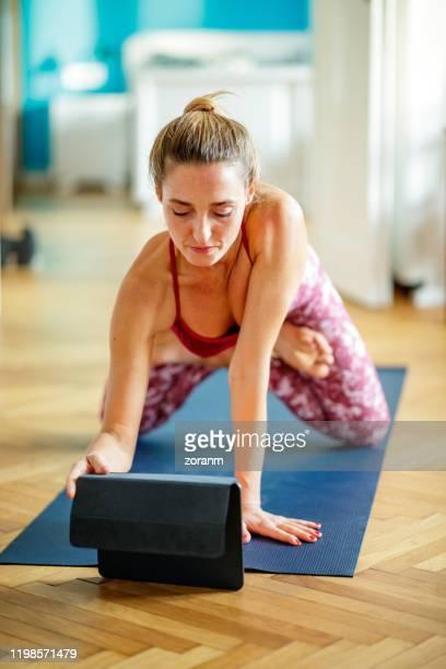 woman trying to follow yoga exercise tutorial - vertical imagens e fotografias de stock