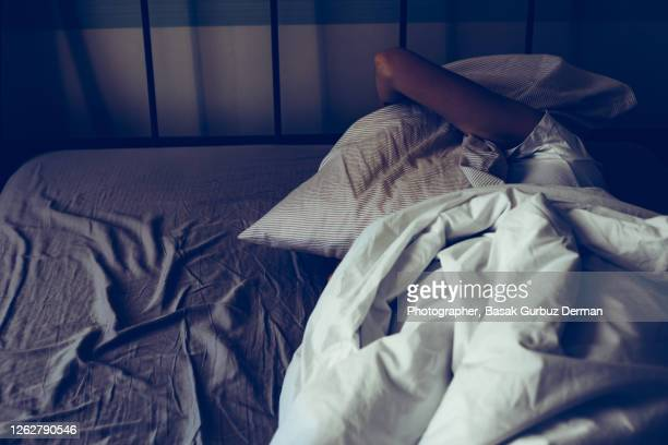 a woman trying to sleep more, having trouble sleeping due to noise, covering her ears with pillow ... - night stock pictures, royalty-free photos & images