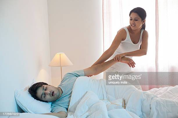 Woman trying to waking up her husband on the bed
