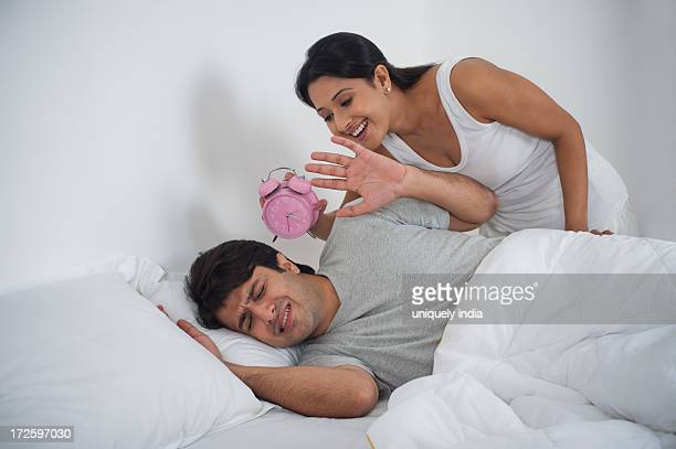 Woman trying to waking up her husband with alarm clock on bed