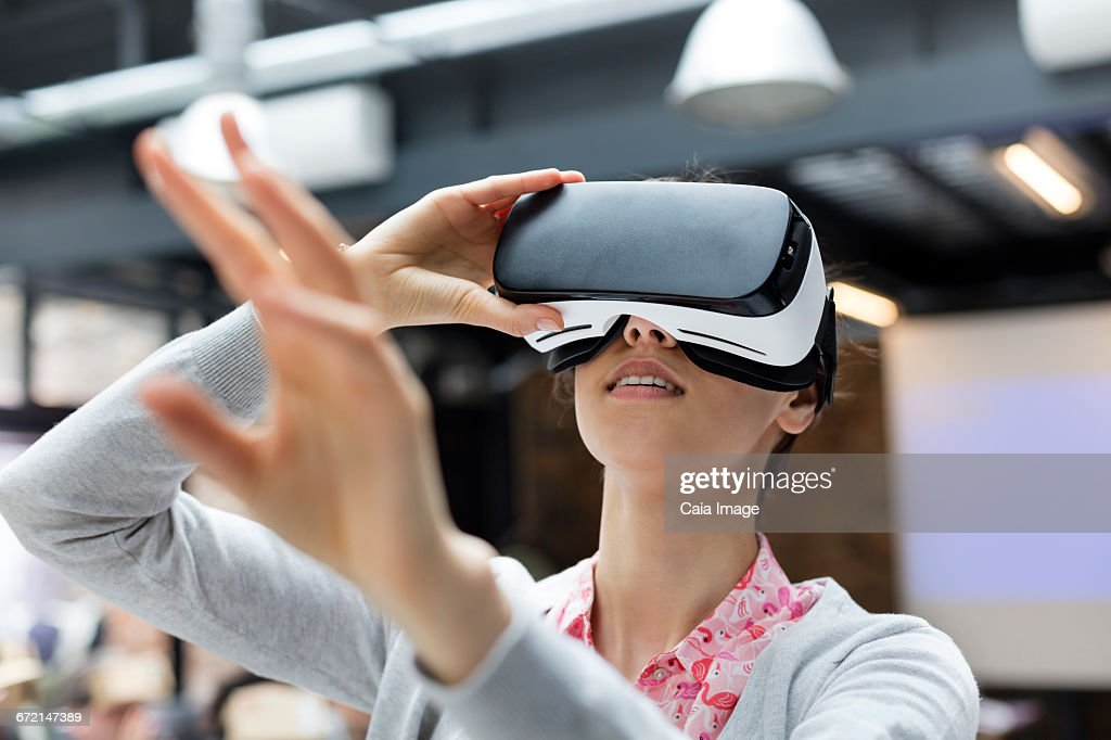 Woman trying virtual reality simulator glasses glasses reaching : Stock Photo