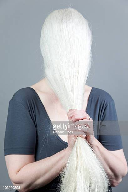 woman tugging at her long white hair - white hair stock pictures, royalty-free photos & images