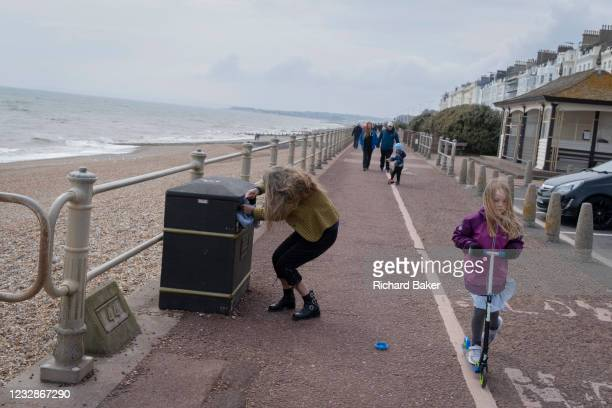 Woman tugs at the plastic bin bag on the seafront at St Leonards, on 3rd May 2021, in St Leonards, Sussex, England.