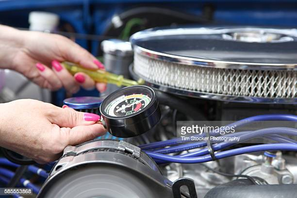 A woman tuning a car engine with a vacuum gauge