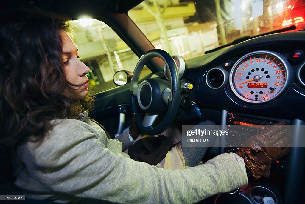 Woman tuning car radio : Stock Photo