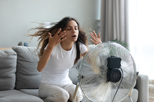 Woman turned on fan waving her hands to cool herself 1192627562