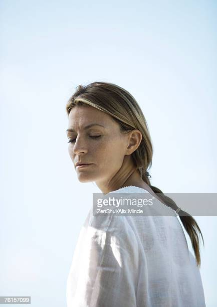 Woman turning head, eyes half-closed, low angle view
