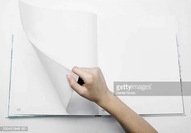 woman turning numbered blank page in photograph album, close-up - turning stock pictures, royalty-free photos & images