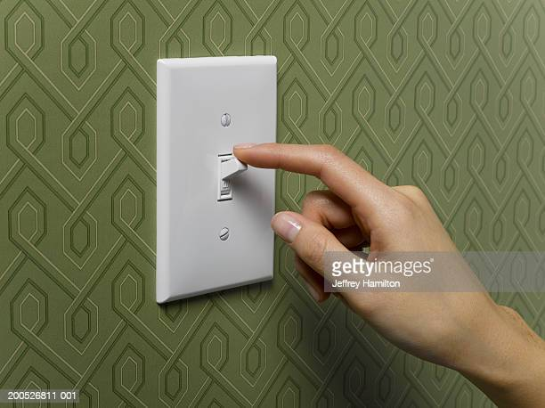 woman turning off light switch on green wallpapered wall, close-up - turning on or off stock pictures, royalty-free photos & images