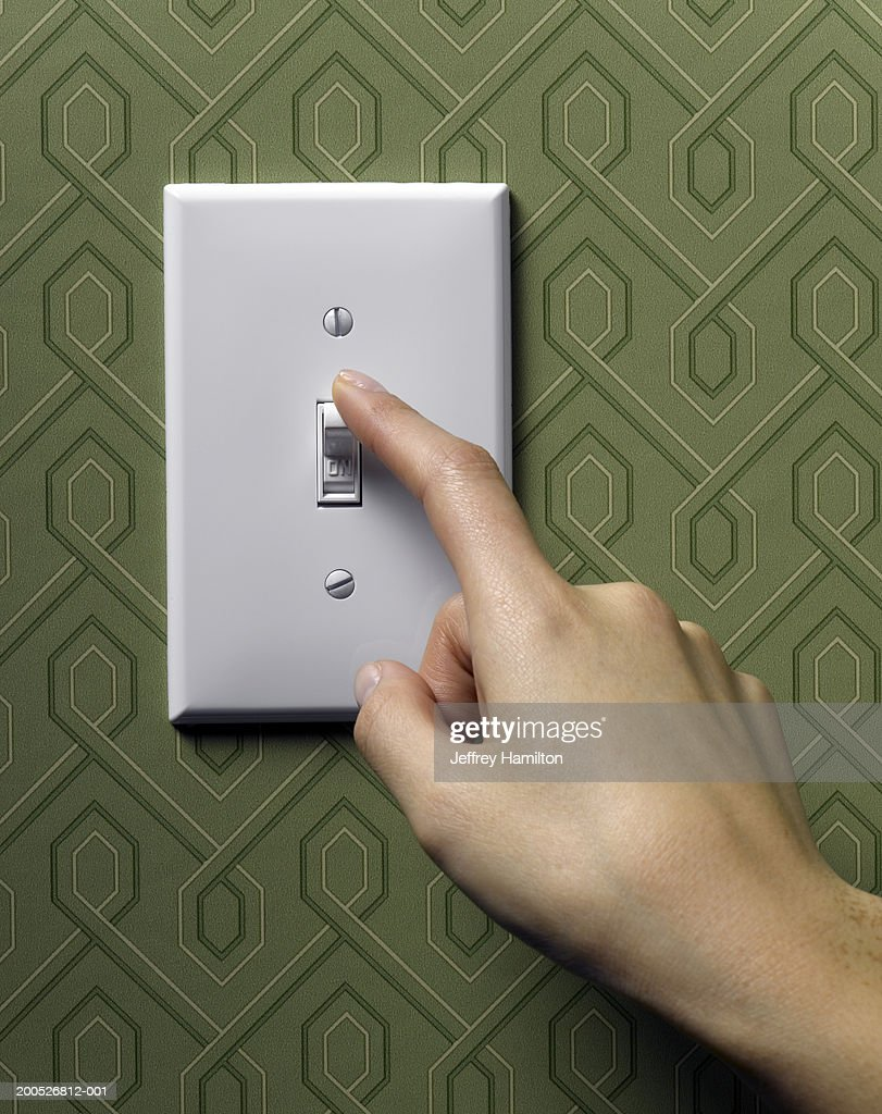 Woman turning off light switch on green wallpapered wall, close-up : Stock Photo