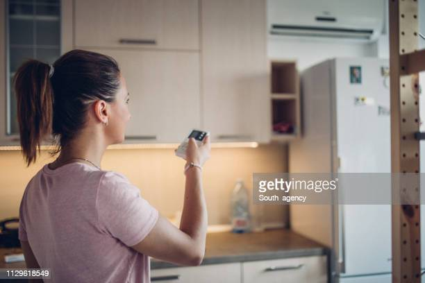 woman turning on air conditioner in kitchen - hair back stock pictures, royalty-free photos & images