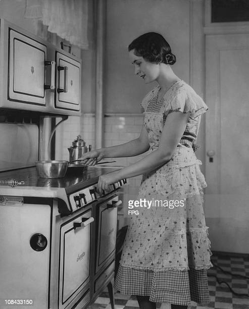 A woman turning on the cooker circa 1940