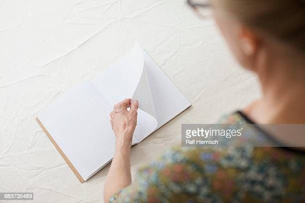 Woman turning page of blank book at table
