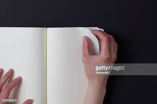 Woman turning page of blank note book