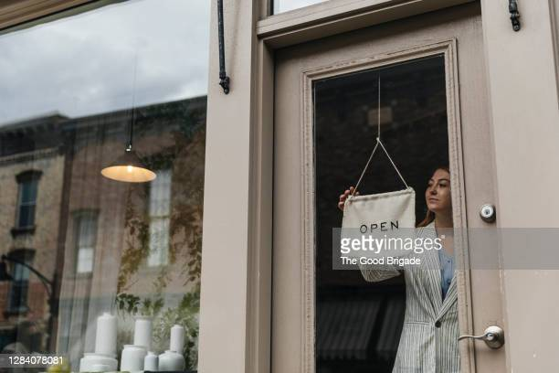 woman turning sign in shop window - open stock pictures, royalty-free photos & images