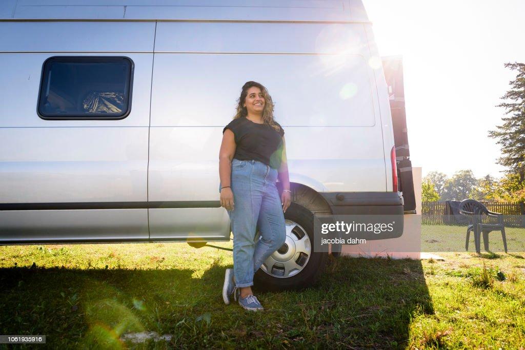 Woman turning van into camper trailer, posing for poirtrait : Stock-Foto