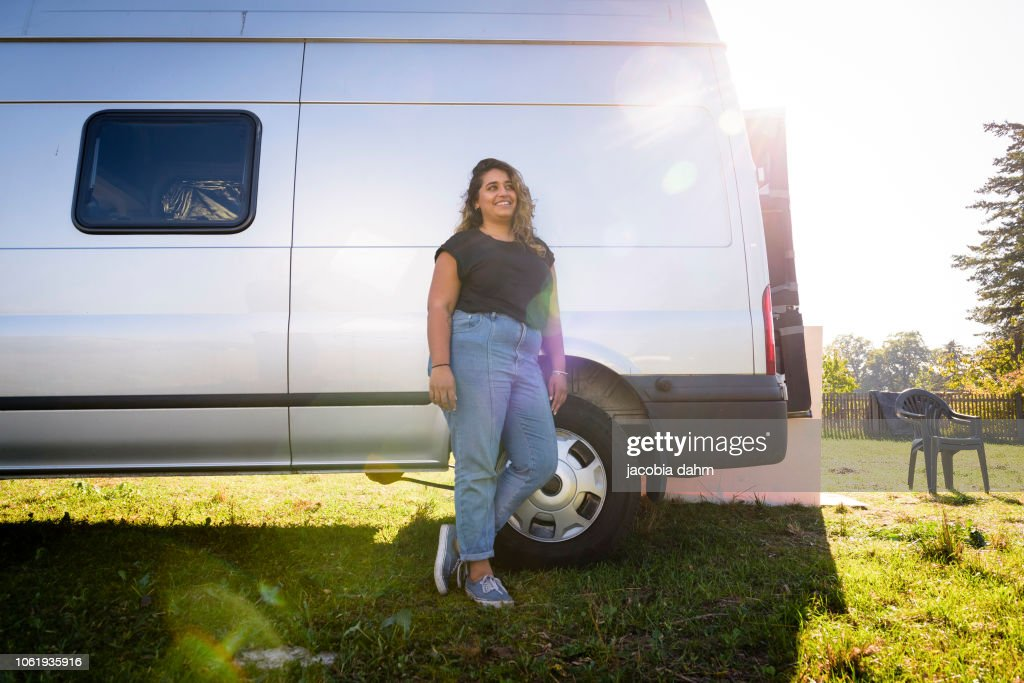 Woman turning van into camper trailer, posing for poirtrait
