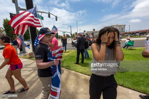 Woman turns away in frustration after arguing with a supporter of President Donald Trump at a pro-police rally as demonstrators across the nation...