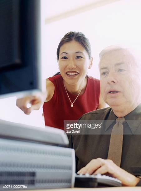 Woman Tutoring Man on Computer