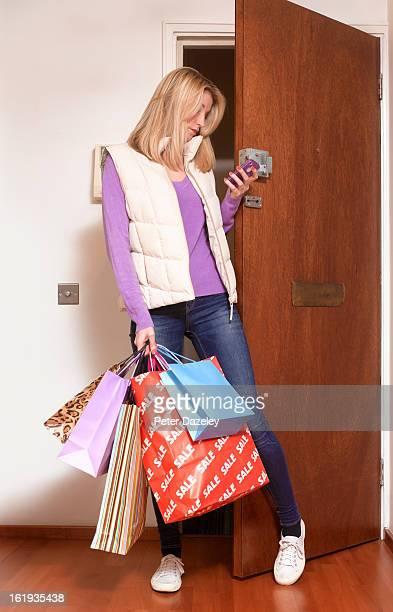 Woman tweeting coming through front door