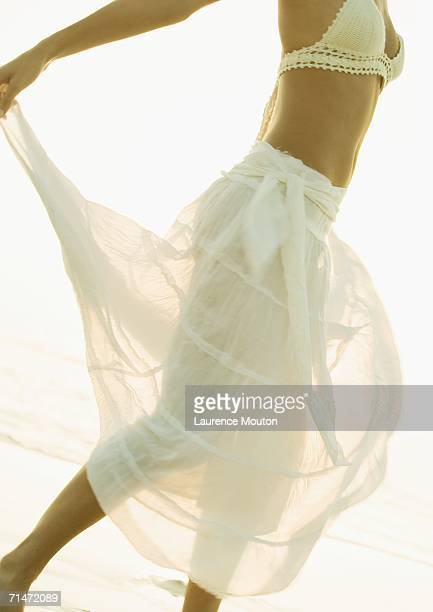 Woman twirling translucent skirt on beach, chest down