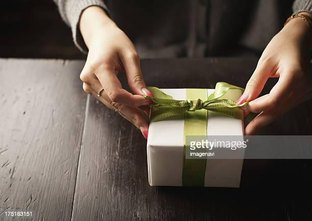 Woman tying a gift box with a ribbon