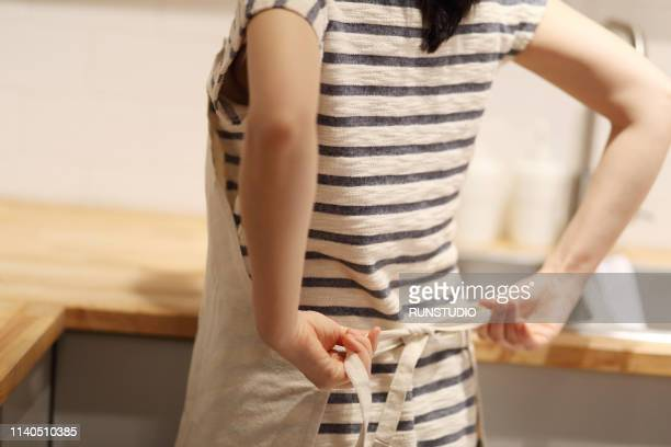 woman tying apron - apron stock pictures, royalty-free photos & images