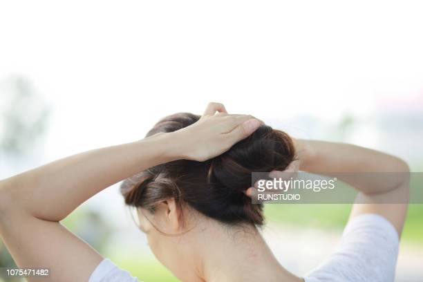 woman tying hair bun - hair back stock pictures, royalty-free photos & images