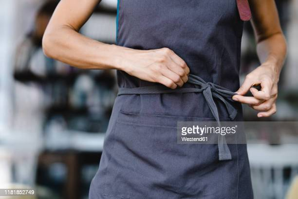 woman tying her apron before work - schürze stock-fotos und bilder