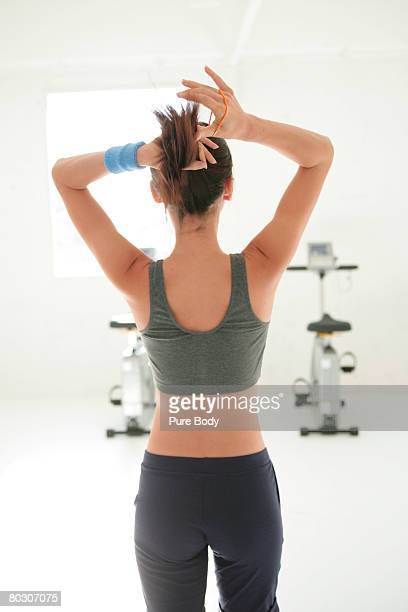 woman tying her hair, rear view - female body hair stock photos and pictures