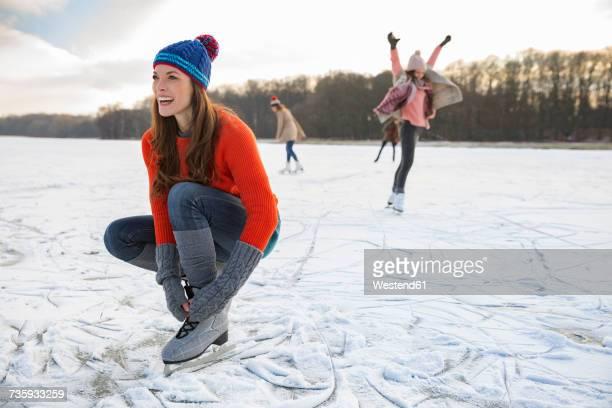 woman tying her ice skates on frozen lake - eislauf oder rollschuhlauf stock-fotos und bilder