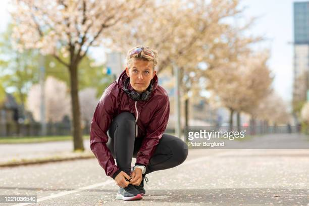 woman tying her sports shoes - windbreak stock pictures, royalty-free photos & images
