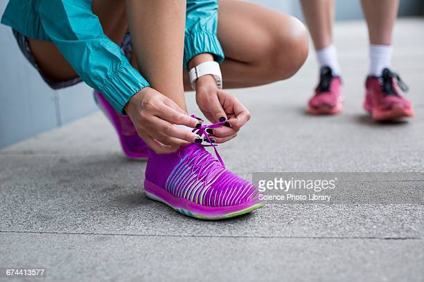 Woman tying laces on trainers