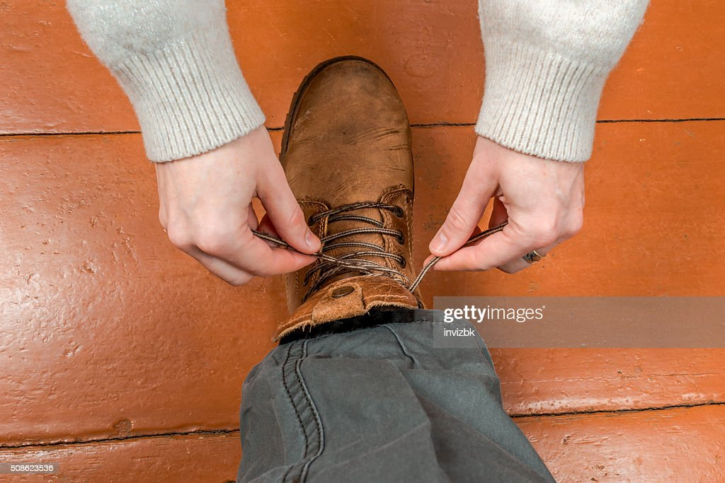 Woman tying male shoelaces : Stock Photo
