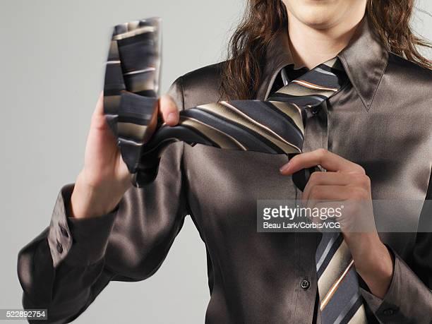 Woman tying necktie