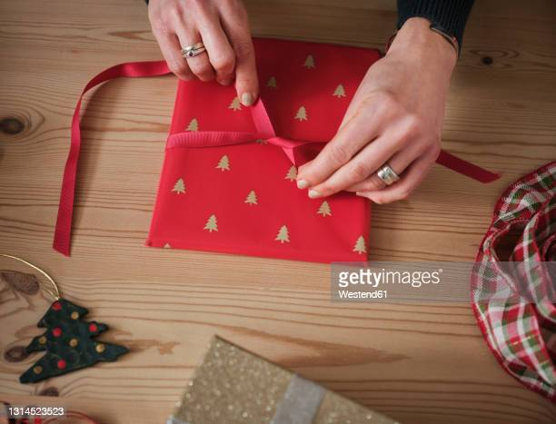woman tying red ribbon on gift over table during christmas - jewellery stock pictures, royalty-free photos & images