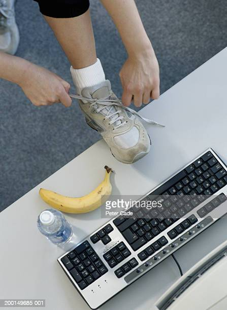 Woman tying shoe lace on desk by computer, elevated view