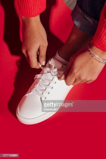 woman tying shoe lace on red background - tying shoelace stock pictures, royalty-free photos & images