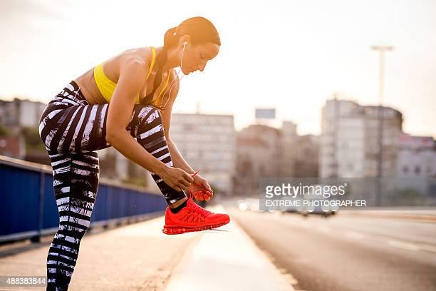 Woman tying shoelace on the bridge
