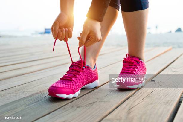 woman tying shoes on the beach - pink shoe stock pictures, royalty-free photos & images
