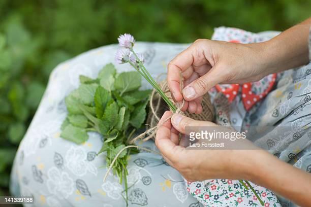 Woman tying string around flowers