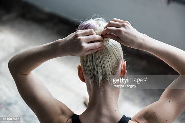Woman tying up hair in studio
