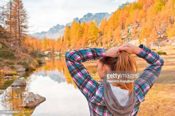 Woman tying up her hair in front of the small lake near Crampiolo known as Witches Lake, Alpe Veglia and Alpe Devero Natural Park, Baceno, Verbano Cusio Ossola province, Piedmont, Italy