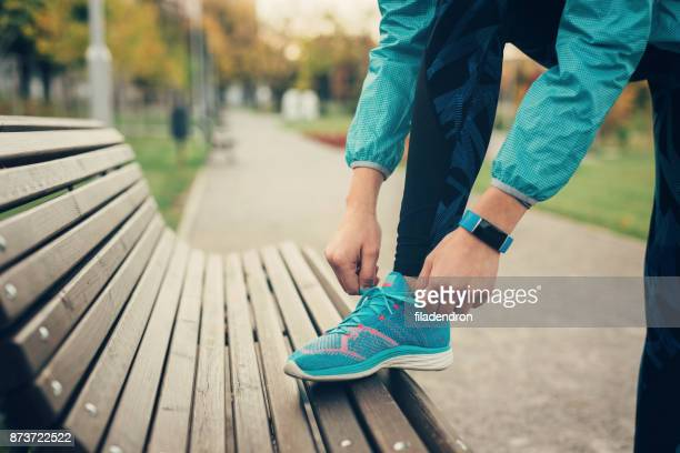 woman tying up her shoe lace - blue shoe stock pictures, royalty-free photos & images