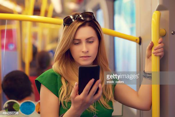 woman typing her phone in the bus